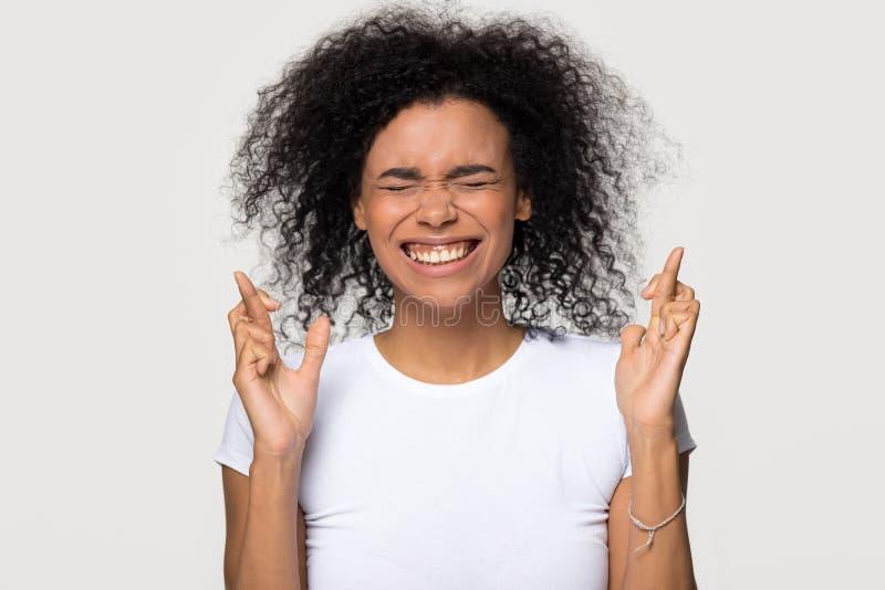 Rolig skrockfull svart kvinna som korsar fingrar som önskar för bra lycka arkivbilder