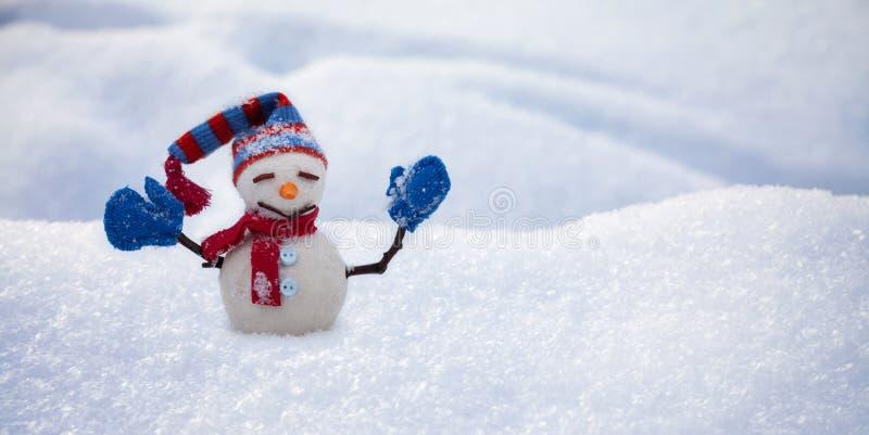 Rolig snögubbe med den röda halsduken för hatt och blåa tumvanten, naturlig snöig fältbakgrund lyckligt glatt nytt ?r f?r jul arkivfoto