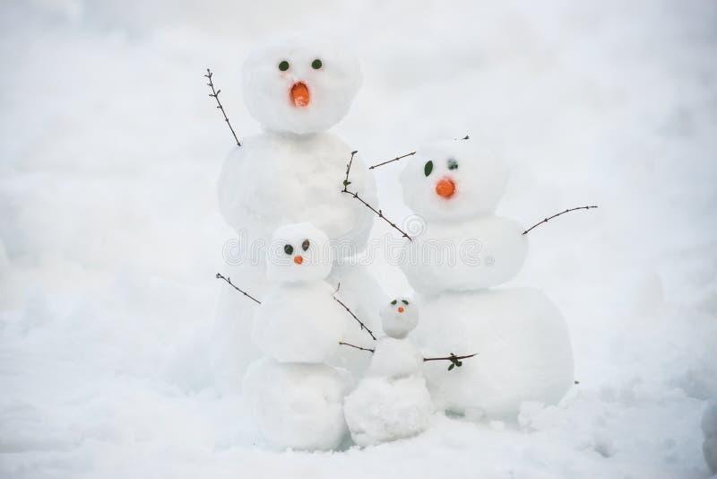 Rolig snögubbefamilj på snön arkivfoton