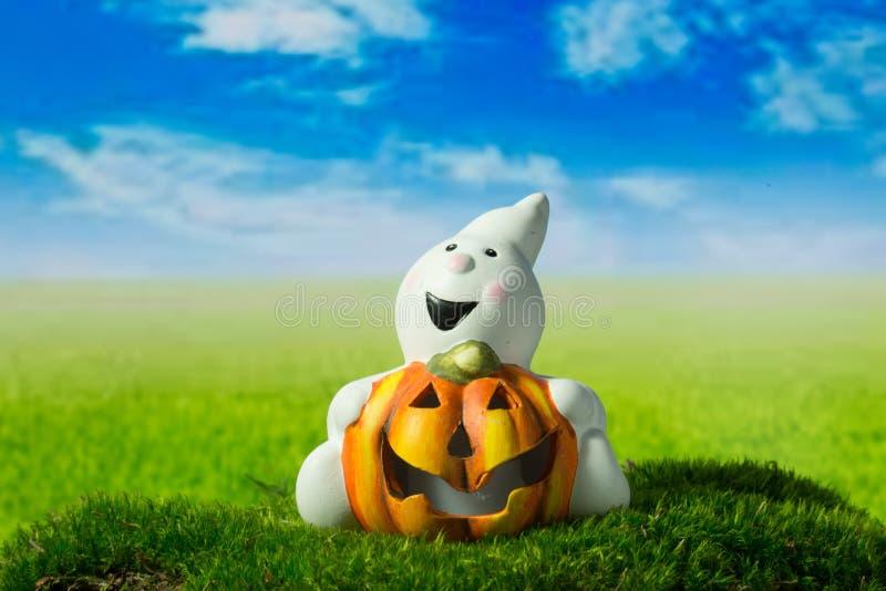 Rolig spöke med pumpa på den gröna ängen på halloween royaltyfria foton