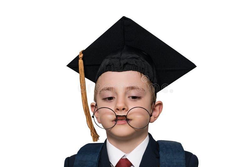 Rolig stående av en skolpojke i en akademisk hatt och stora exponeringsglas isolate skola f?r copyspace f?r begrepp f?r svarta b? royaltyfria bilder