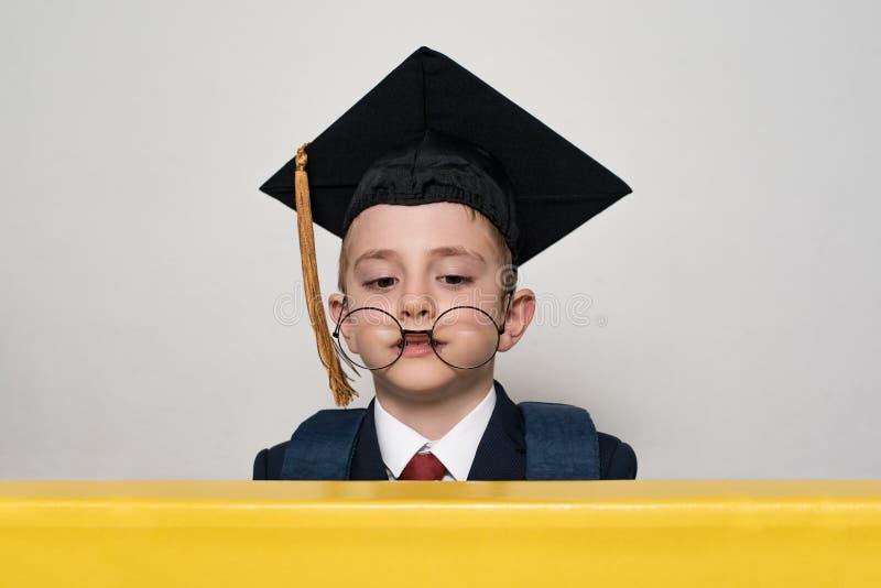 Rolig stående av en skolpojke i en akademisk hatt och stora exponeringsglas Vit bakgrund skola f?r copyspace f?r begrepp f?r svar arkivbild