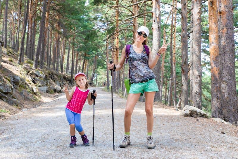 Rolig stående av kvinnan och lilla flickan som poserar med segersymbol i händer i skog av Madrid royaltyfri foto