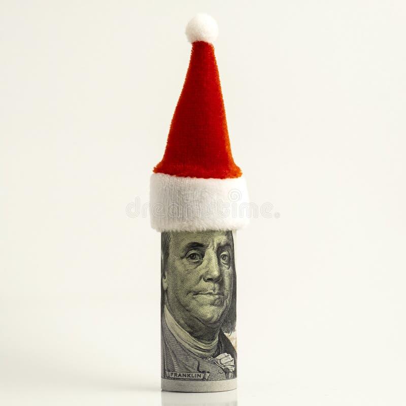 Rolig stående av presidenten Franklin Hundra-dollaren räkningen är hoprullad och den röda Santa Claus hatten upptill finansiellt royaltyfri fotografi