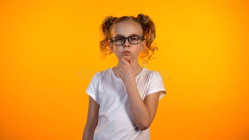 Rolig tonårs- flicka som rymmer hakan och tänker, liten snille som framkallar ny idé arkivbilder