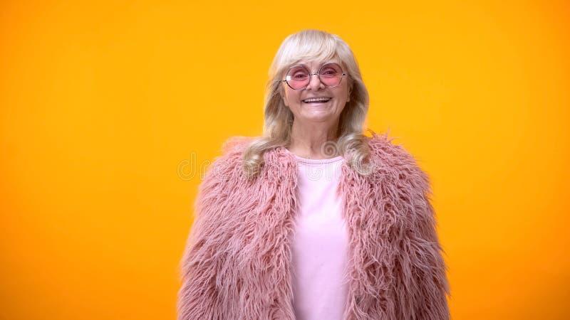 Rolig trendig åldrig dam i rosa lag och rund solglasögon som ler på kamera royaltyfri bild
