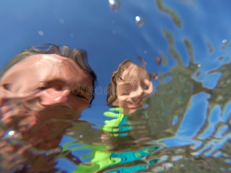 Rolig undervattens- stående av en fader och hennes dotter royaltyfri foto