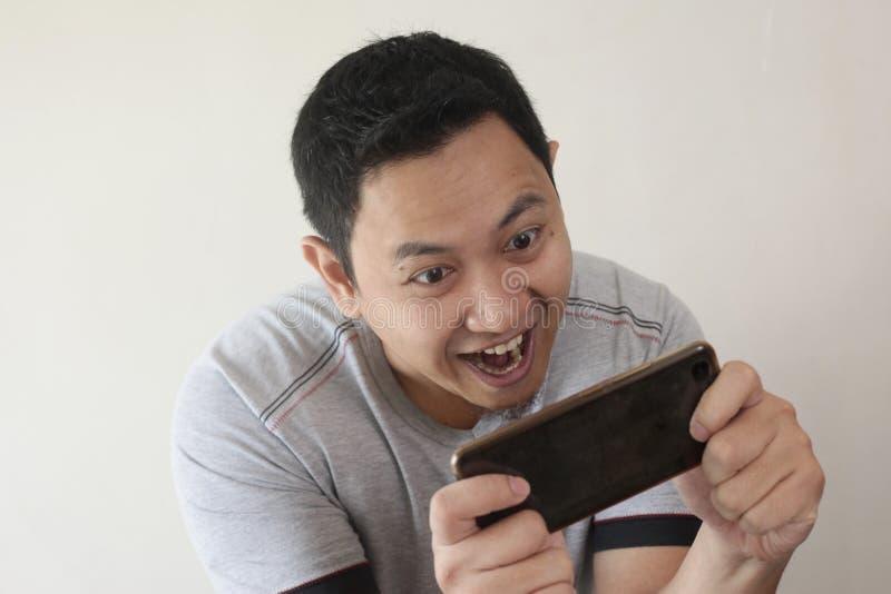 Rolig ung asiat Guy Playing Games på den smarta telefonen för minnestavla royaltyfria bilder