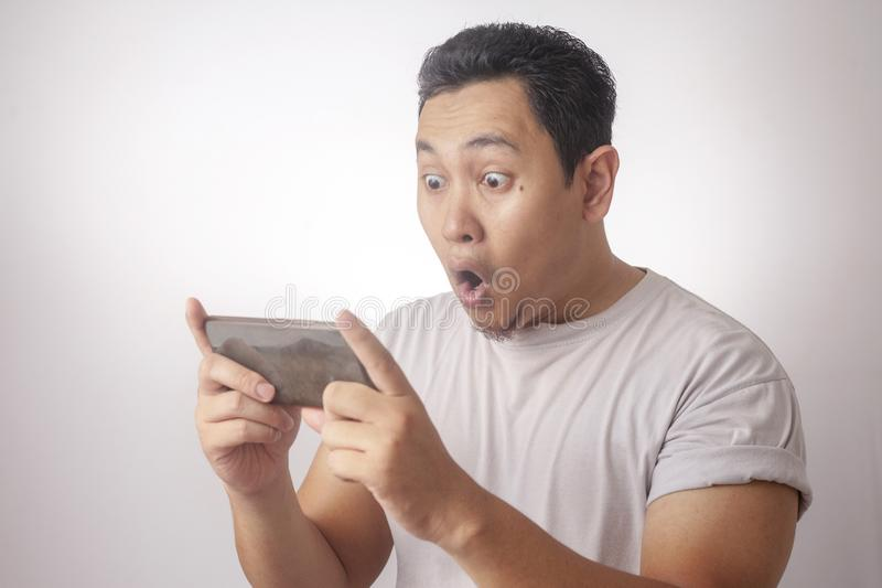 Rolig ung asiat Guy Playing Games p? den smarta telefonen f?r minnestavla royaltyfri bild