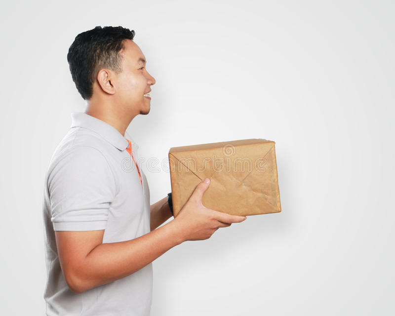 Rolig ung asiatisk kurir Guy Giving Package Box royaltyfria foton