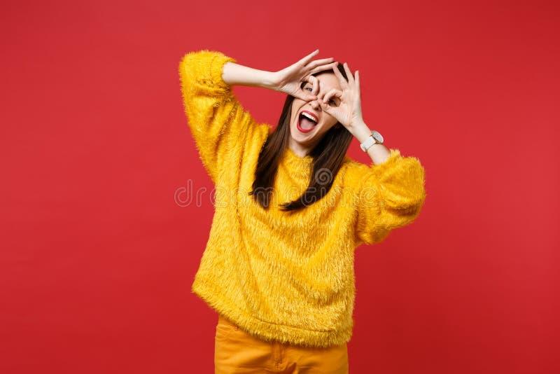 Rolig ung kvinna i den gula pälströjan som rymmer händer nära ögon och att imitera exponeringsglas eller kikare som isoleras på l royaltyfri foto