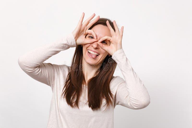 Rolig ung kvinna i ljus kläder som rymmer händer nära ögon och att imitera exponeringsglas eller kikare som visar tungan som isol royaltyfria foton
