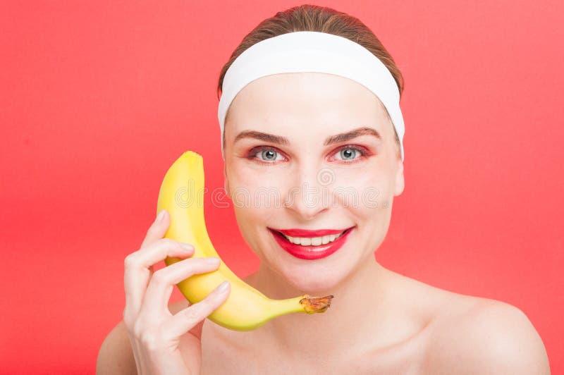 Rolig ung kvinna med bananen nära henne royaltyfria foton