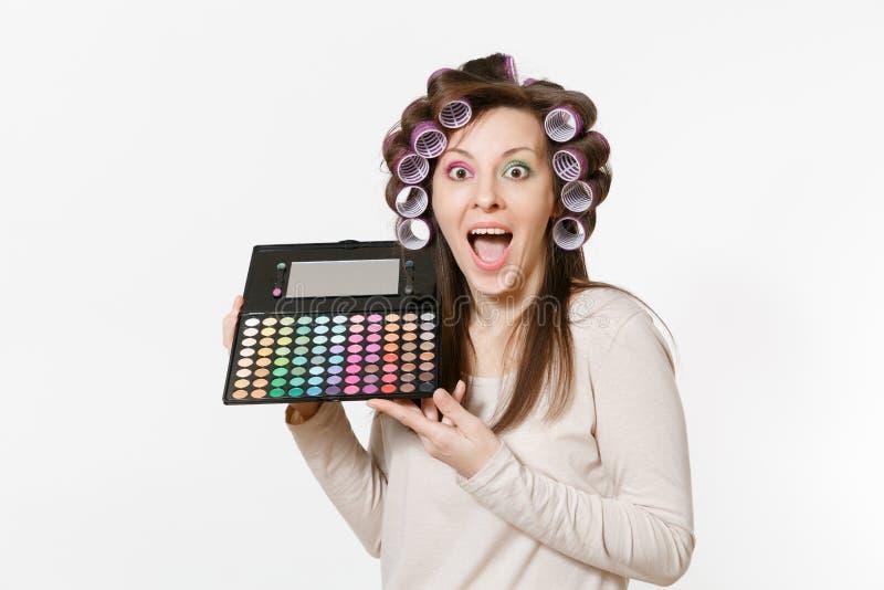 Rolig ung kvinna med hårrullar på hår med färgrika ögonskuggor för palett som isoleras på vit bakgrund Makeup med uppsättningen arkivbild