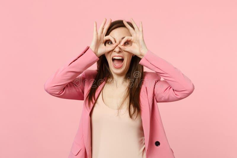 Rolig ung kvinna som vitt håller munnen öppen och att rymma händer nära ögon och att imitera exponeringsglas eller kikare på past royaltyfria foton