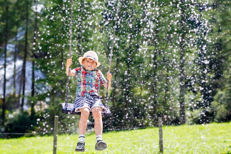 Rolig ungepojke som har gyckel med chain gunga på utomhus- lekplats, medan vara vått som plaskas med vatten barn som svänger på royaltyfri fotografi