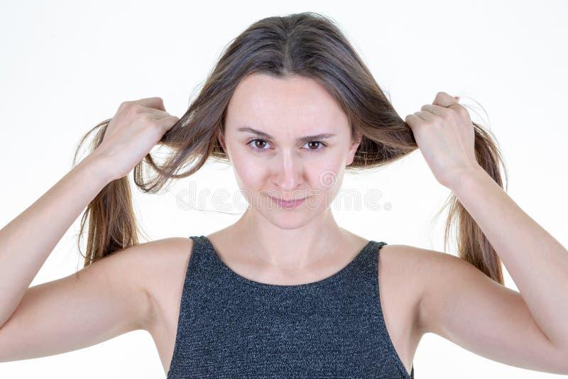 Rolig vuxen flicka som har gyckel och gör två hästsvansar med hennes bruna hår över vit bakgrund arkivfoto
