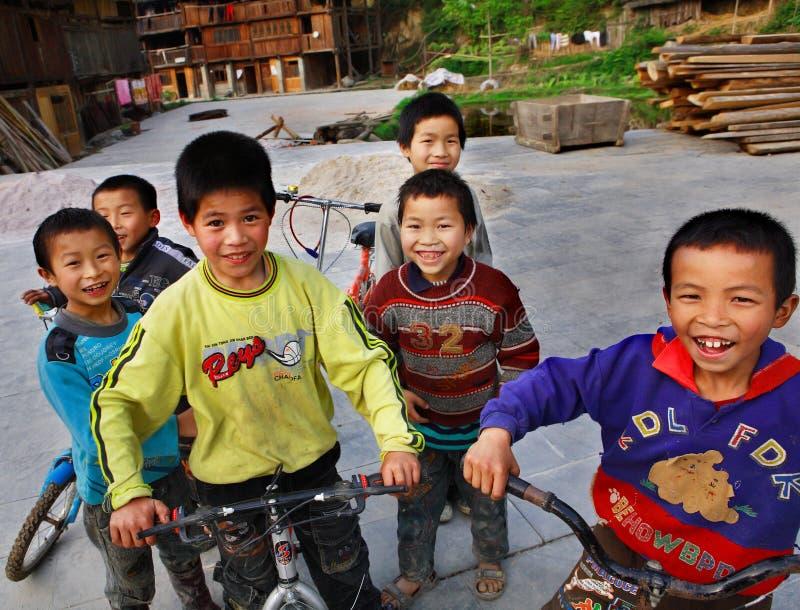 Roliga asiatiska barn från landsbygder av Kina, ritt cyklar. arkivfoto