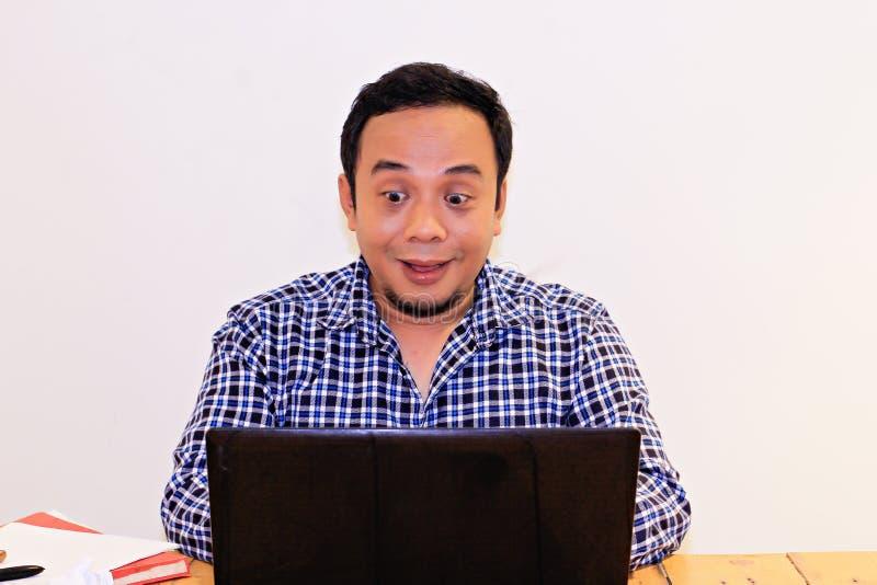 Roliga asiatiska mäns uttryck, när se något på hans bärbar dator royaltyfri foto