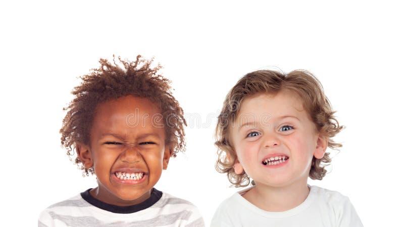 Roliga barn som gör framsidor med avsmak royaltyfria foton
