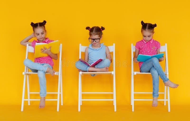 Roliga barnflickor läste böcker på kulör gul bakgrund royaltyfri fotografi