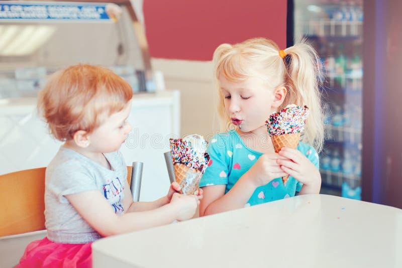 Roliga barnflickor som sitter dela tillsammans glass royaltyfria bilder
