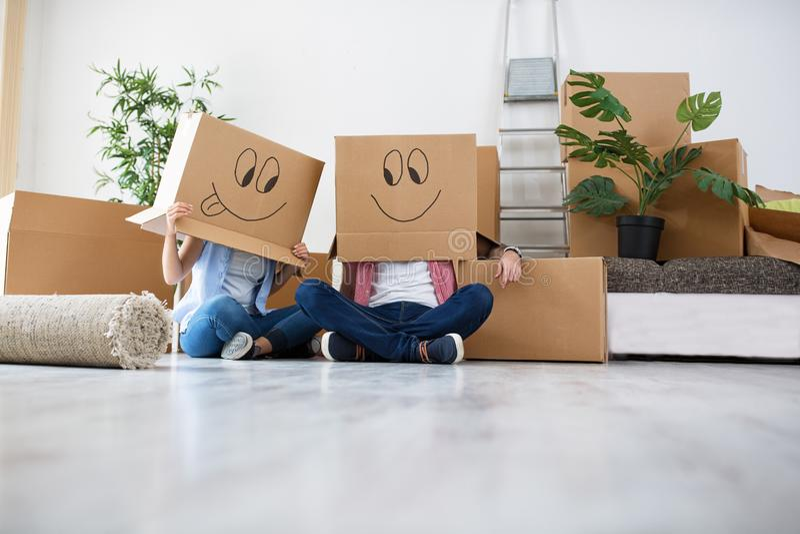 Roliga barnpar tycker om och fira att flytta sig till det nya hemmet arkivbilder