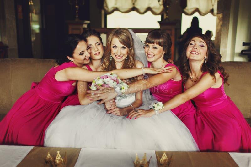 Roliga brudlloks, medan brudtärnor i rosa klänningar rymmer hennes vei royaltyfri foto