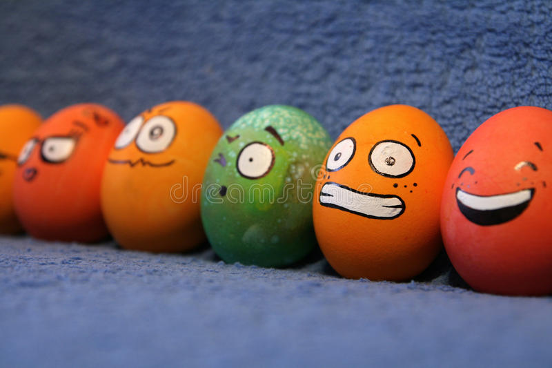 Roliga färgrika påskägg med framsidor fotografering för bildbyråer