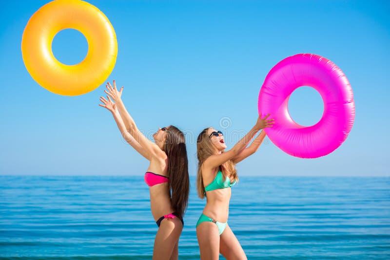 Roliga flickavänner solbadar på stranden royaltyfria foton