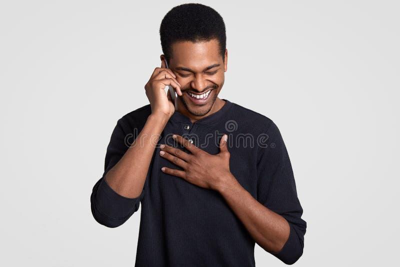 Roliga glade mörka flådde manliga skratt lyckligt, hör komisk berättelse från vän på mobiltelefonen, håller händer på bröstkorg,  fotografering för bildbyråer