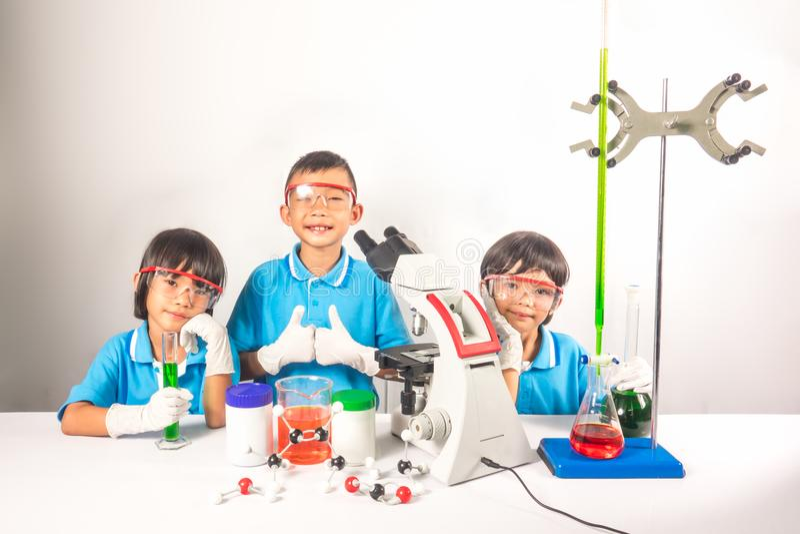 Roliga och lyckliga ungar i vetenskap som lutar på vit bakgrund arkivbild