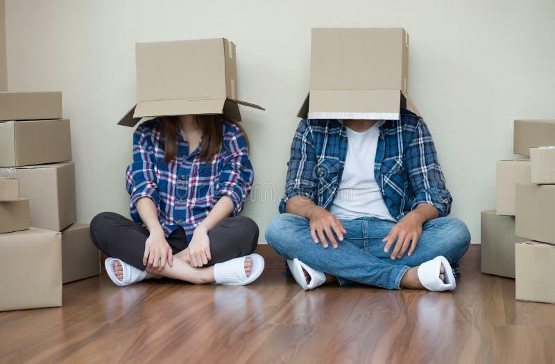 Roliga par flyttar sig med tomma kartonger på deras huvudsitt royaltyfri fotografi