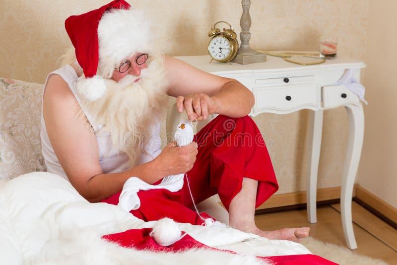 Roliga Santa Claus som lagar sockor arkivfoton