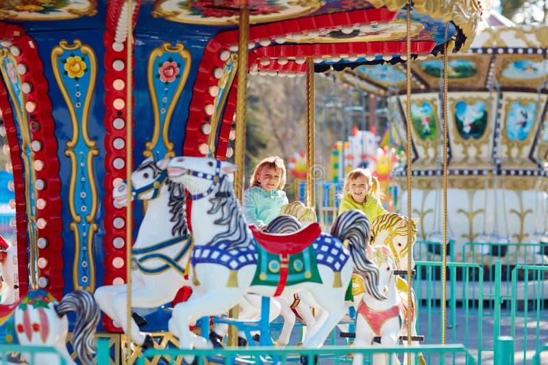 Roliga små flickor på karusell fotografering för bildbyråer
