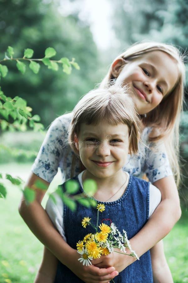Roliga små systrar i sommar parkerar royaltyfri fotografi