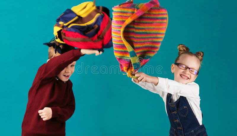 Roliga små ungar med stor ryggsäckbanhoppning och hagyckel igen royaltyfria foton