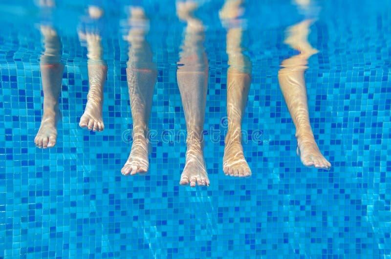 Roliga undervattens- familjben i simbassäng royaltyfri fotografi
