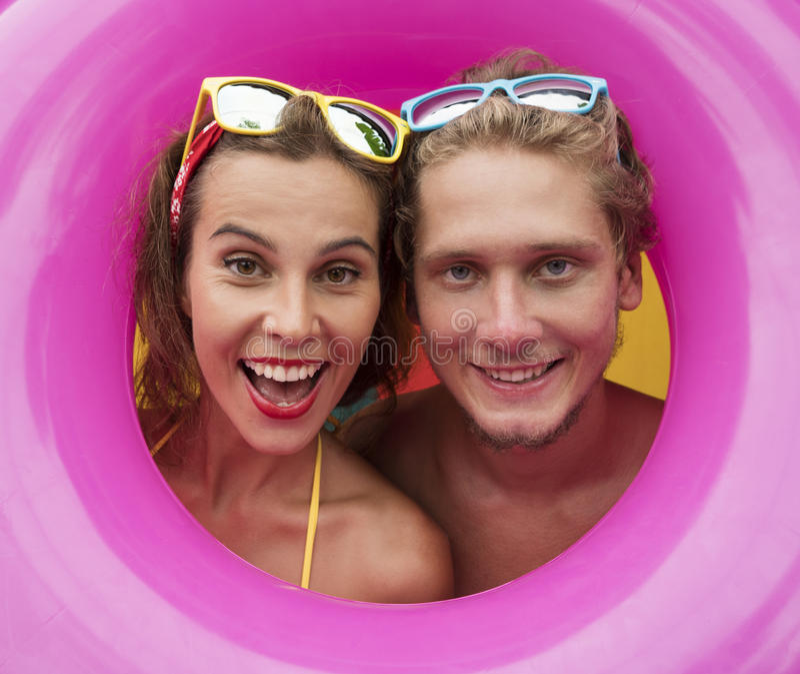 Roliga unga lyckliga strandpar som ler i mitt av den rosa uppblåsbara cirkeln arkivbilder