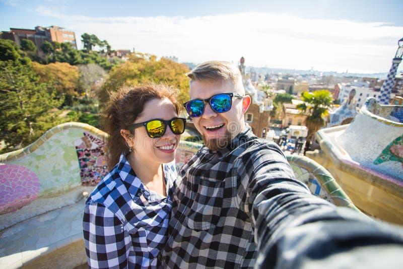 Roliga unga par som ser kameran som tar fotoet med den smarta telefonen som in ler, parkerar Guell, Barcelona, Spanien arkivfoton