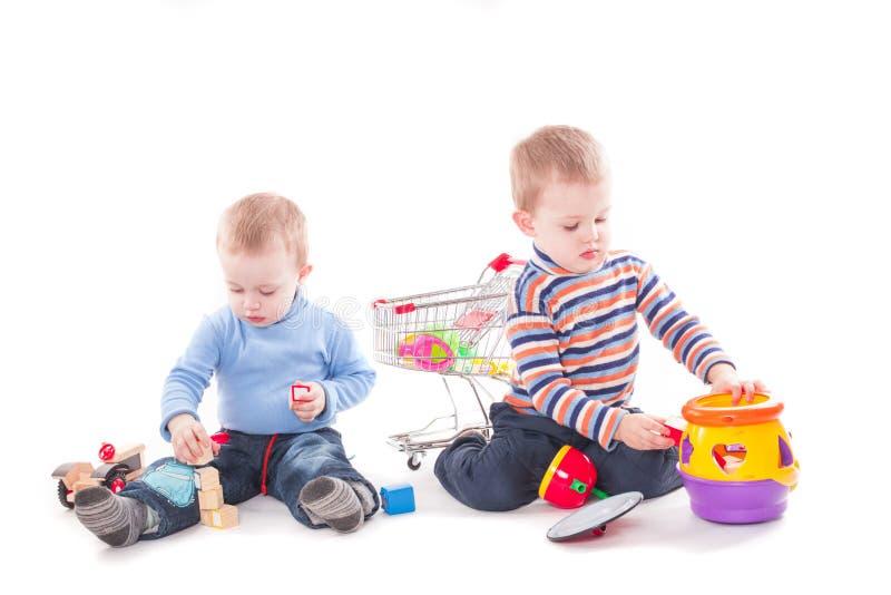 Roliga ungar som spelar bildande leksaker royaltyfri foto