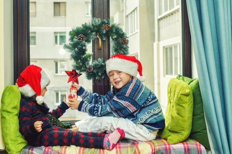 Roliga ungar som spelar på fönstret på julferier arkivfoton