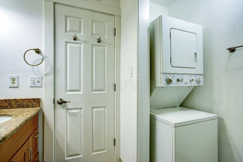 Roligt badrum med badrumfåfänga och staplad packning och tork royaltyfria foton