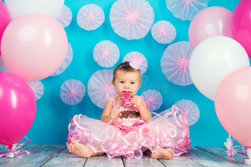 Roligt barn med en klubba i formen av en hjärta, lycklig liten flicka royaltyfri foto