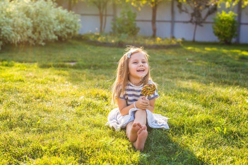 Roligt barn med godisklubban, lycklig liten flicka som äter den stora sockergodisen royaltyfri bild