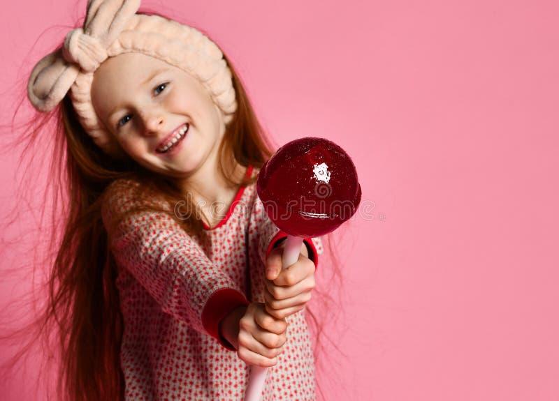 Roligt barn med godisklubban, lycklig liten flicka som äter den stora sockerklubban arkivfoto