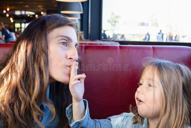 Roligt barn som äter och ger en stekt potatis till hennes moder som sitter i restaurang royaltyfri fotografi