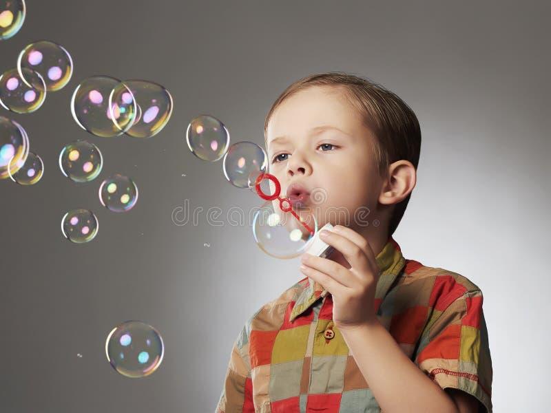 Roligt barn som blåser såpbubblor pojke little arkivfoton