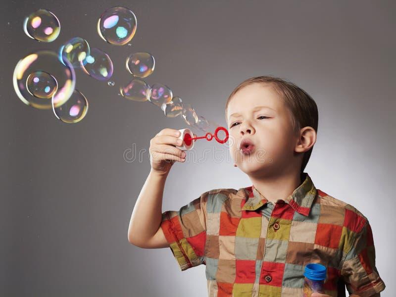 Roligt barn som blåser såpbubblor pojke little arkivbild