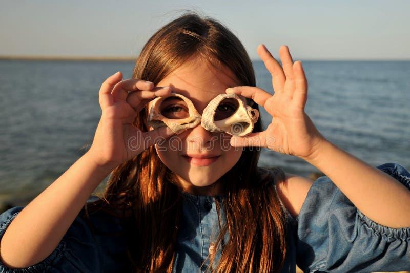 Roligt begrepp för sommar med ståenden av en flicka med skal på en strand royaltyfri fotografi
